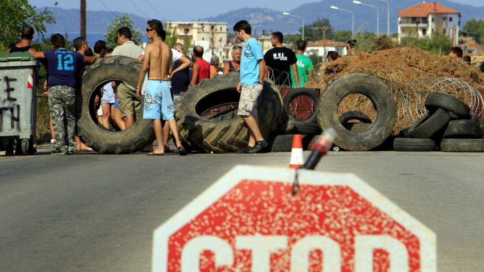 A stop sign is placed at a barricade set up by residents at the village of Ierissos on the northern peninsula of Halkidiki, Greece where demonstrators oppose the development of a gold mine in the area by Canadian firm Eldorado Gold, in this photo taken on July 10, 2013. (AP / Nikolas Giakoumidis)