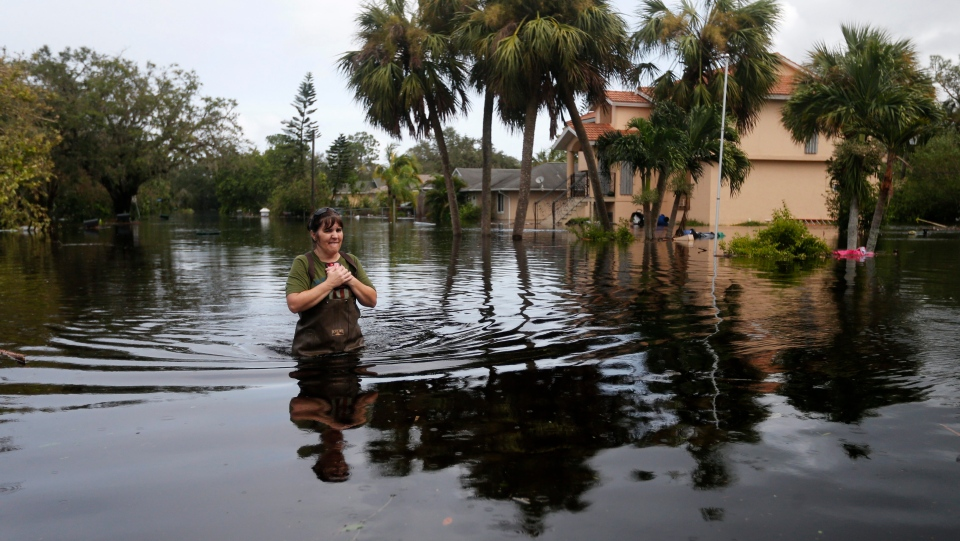 Kelly McClenthen walks through her flooded neighborhood, as she returns to see the damage to her home in the aftermath of Hurricane Irma in Bonita Springs, Fla., Monday, Sept. 11, 2017. (AP Photo/Gerald Herbert)