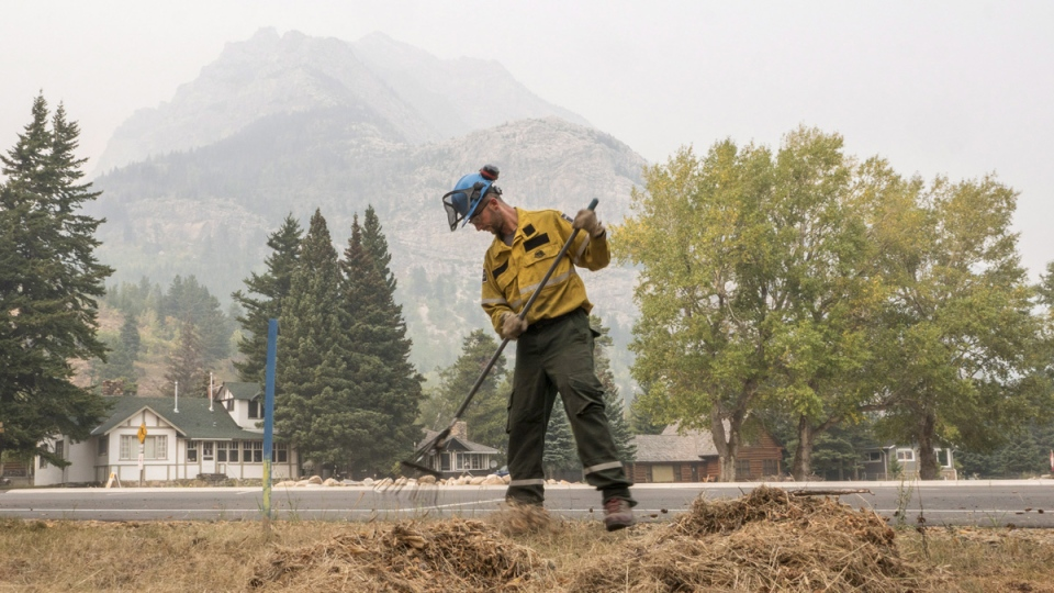 A fire crew member rakes up dead grass near the town of Waterton, Alta. (Parks Canada, Nicholas Alexander / THE CANADIAN PRESS)