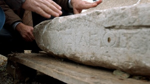 FILE -- Archaeologist Vassilis Aravantinos, wearing a brown jacket, and a culture ministry employee examine an inscription bearing the word 'king' in Greek, found at among remains of an Roman battle monument, in Orchomenos, central Greece, on Wednesday, Dec. 8, 2004. (AP Photo/Thanassis Stavrakis)