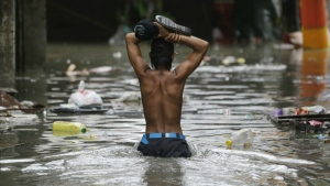 A resident wades through a flooded street as he returns to his home in Manila, Philippines on Tuesday, Sept. 12, 2017. (AP / Aaron Favila)