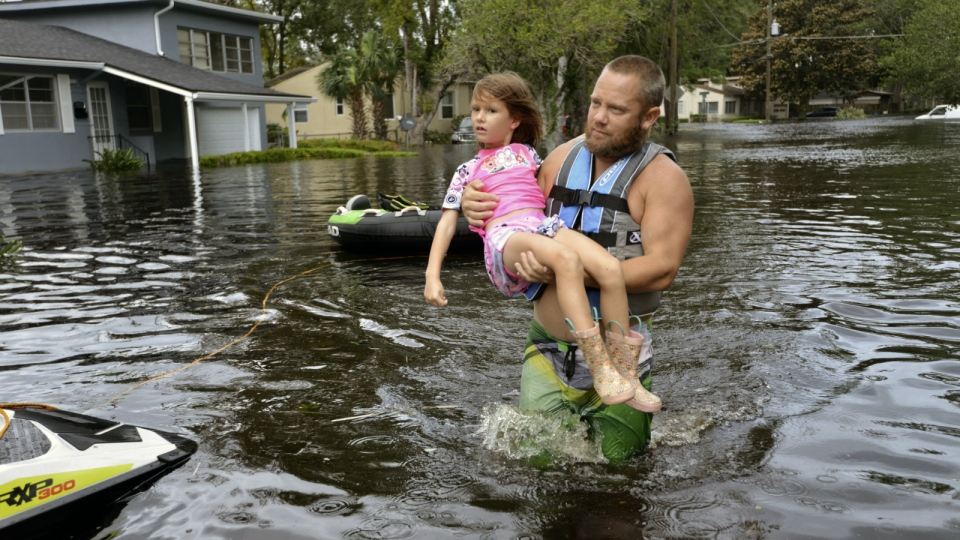 Tommy Nevitt carries Miranda Abbott, 6, through floodwater caused by Hurricane Irma on the west side of Jacksonville, Fla. on Monday, Sept. 11 2017. (Dede Smith / The Florida Times-Union)