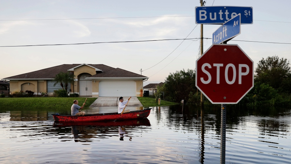 Pierre Ghantos, left, and his son Nathan paddle though their flooded neighbourhood in the aftermath of Hurricane Irma in Fort Myers, Fla., Tuesday, Sept. 12, 2017. (AP / David Goldman)
