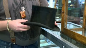 Antique store owner Clinton Beck holds a top hat that he recently realized was stolen from a museum