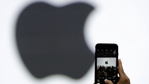 In this Monday, June 5, 2017, file photo, a person takes a photo of an Apple logo before an announcement of new products at the Apple Worldwide Developers Conference in San Jose, Calif.  (AP Photo/Marcio Jose Sanchez, File)