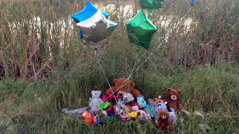 Stuffed animals and balloons sit at a pond near Dundonald School in Saskatoon on Tuesday, Sept. 12, 2017, one day after a five-year-old boy, pronounced dead in hospital, was found in the pond. (Fiona Odlum/CTV Saskatoon)