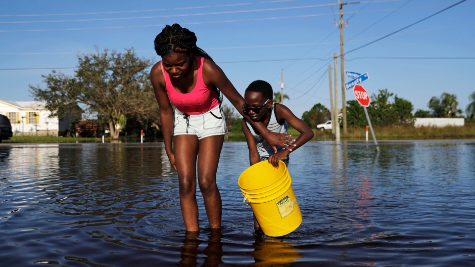 Nineve Desronvil, 20, left, and her brother Jeffrey 8, wade through their flooded street trying to catch fish in the aftermath of Hurricane Irma in Fort Myers, Fla., Wednesday, Sept. 13, 2017. (AP Photo/David Goldman)