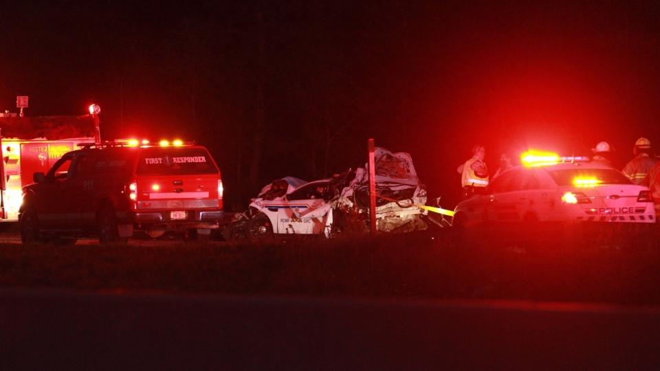 Rescue vehicles and workers are shown on the scene of a fatal accident near Memramcook, N.B., Tuesday, Sept.12, 2017. A member of the Nova Scotia RCMP is dead following a collision in southeastern New Brunswick. (THE CANADIAN PRESS/John Morris)
