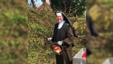 Sister Margaret Ann holds a chainsaw