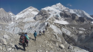 In this Monday, Feb. 22, 2016 file photo, international trekkers pass through a glacier at the Mount Everest base camp, Nepal. Scientists say a third of the ice stored in Asia's glaciers will be lost by the end of the century even if global warming stays below 1.5 degrees Celsius. (AP Photo/Tashi Sherpa, file)
