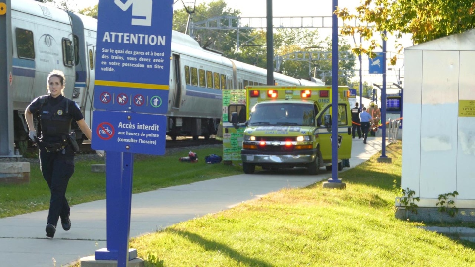 A police officer runs down a path in front of an ambulance at the Roxboro-Pierrefonds train station on Sept. 12, 2017 (Pascal Marchand)
