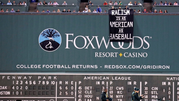 Fans drop a sign at the Green monster
