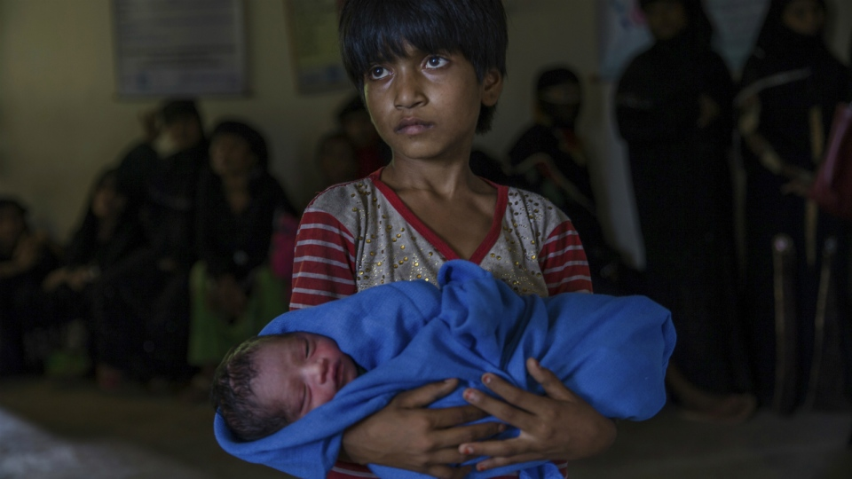 Rohingya Muslim girl Afeefa Bebi, who recently crossed over from Myanmar into Bangladesh, holds her few-hours-old brother as doctors check her mother Yasmeen Ara at a community hospital in Kutupalong refugee camp, Bangladesh on Wednesday, Sept. 13, 2017. (AP / Dar Yasin)