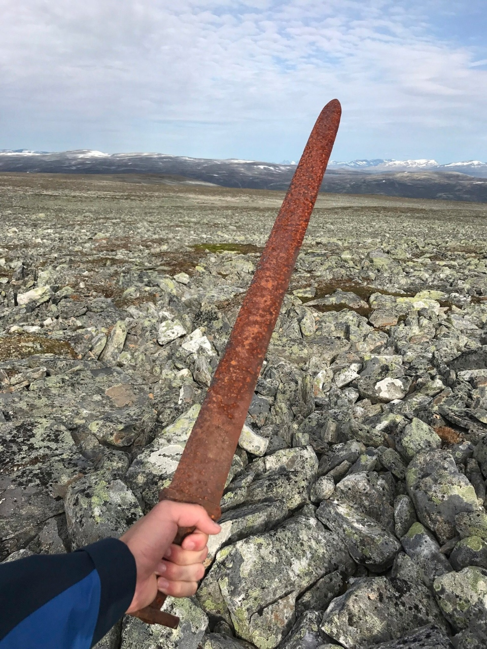 In this photo taken on Aug. 23, 2017, Einar Ambakk, one of the hunters that found an ancient Viking sword slid down between rocks during a reindeer hunt, raises it in Lesja, some 275 kilometers north of Oslo. (Einar Ambakk via AP)