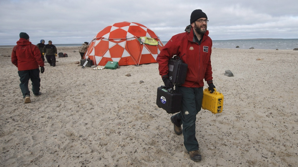 Ryan Harris, Parks Canada, lead underwater archeologist for the Erebus and Terror carries equipment to thew plane at Davit camp on Saunitalik Island near Gjoa Haven Nunavut, on Sept. 1, 2017. (Jason Franson / THE CANADIAN PRESS)