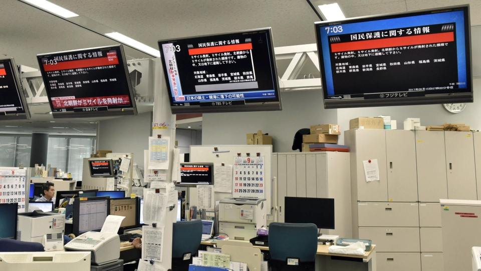 TV monitors show the J-Alert (warning siren) at an office of Kyodo News in Tokyo Friday, Sept. 15, 2017. (Toshiyuki Kuwana / Kyodo News via AP)