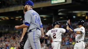 Toronto Blue Jays pitcher Brett Anderson, left, returns to the mound after backing up the play while Minnesota Twins' Brian Dozier, left, and Ehire Adrianza celebrate after they scored on a two-run single by Jorge Polanco off Anderson in the fifth inning of a baseball game in Minneapolis on Thursday, Sept. 14, 2017. (AP / Jim Mone)
