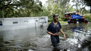 Christopher Taylor walks through the flood waters from Hurricane Irma as his uncles trailer is pulled out of the water on his families land off Lake Shore Drive in Gainesville, Fla. on Thursday Sept. 14, 2017. (Brad McClenny / The Gainesville Sun)