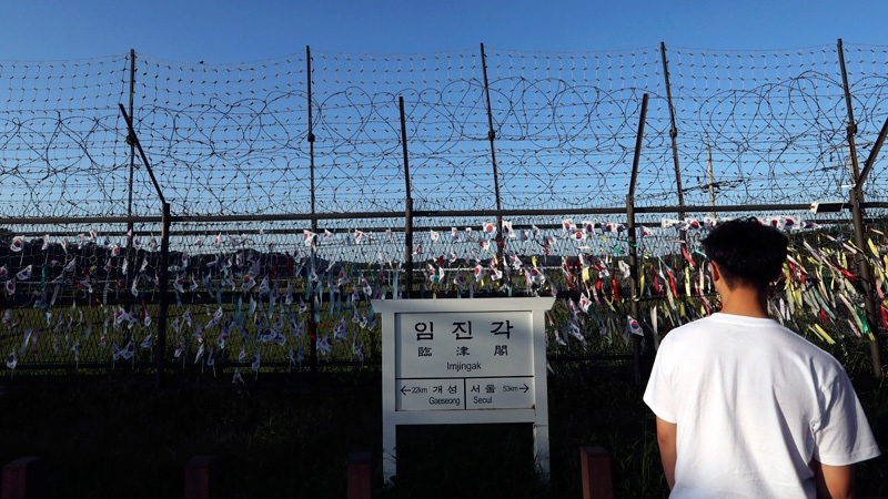 A man walks by the wire fences adorned with national flags near an information sign showing the distance to North Korea's Kaesong city and South Korea's capital Seoul at the Imjingak Pavilion in Paju, South Korea, Friday, Sept. 15, 2017.  (AP /Lee Jin-man)