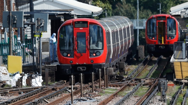 A police forensic officer stands beside the train, at left, where an incident happened, that police say they are investigating as a terrorist attack, at Parsons Green subway station in London, Friday, Sept. 15, 2017. (AP / Frank Augstein)
