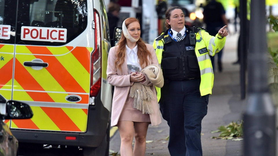 An injured woman is assisted by a police officer close to Parsons Green station in west London after an explosion on a packed London Underground train, Friday, Sept. 15, 2017. (Dominic Lipinski/PA via AP)