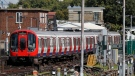 A police forensic officer stands at right near the train, at left, where an incident happened that police say they are investigating as a terrorist attack, at Parsons Green subway station in London, Friday, Sept. 15, 2017. (AP Photo/Frank Augstein)