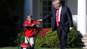 U.S. President Donald Trump walks with Frank Giaccio, 11, of Falls Church, Va., left, as he mows the lawn of the Rose Garden, Friday, Sept. 15, 2017, at the White House in Washington. (AP / Jacquelyn Martin)