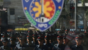 New police trainees are reflected on glass at the Caloocan City Police Station in metropolitan Manila, Philippines on Friday, Sept. 15, 2017. (AP / Aaron Favila)