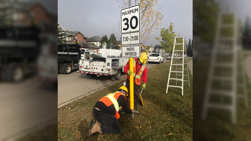 Crews install a Playground Zone sign on Haddow Drive on Friday, September 15, 2017.