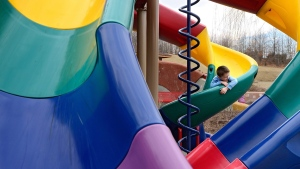 Blake Parrish, 3, looks over the side of the slide while enjoying the warm weather at the Dream Come True Playground, in  in Harrisonburg, Va., on Tuesday, March 11, 2014. (AP Photo/The Daily News-Record, Jason Lenhart)