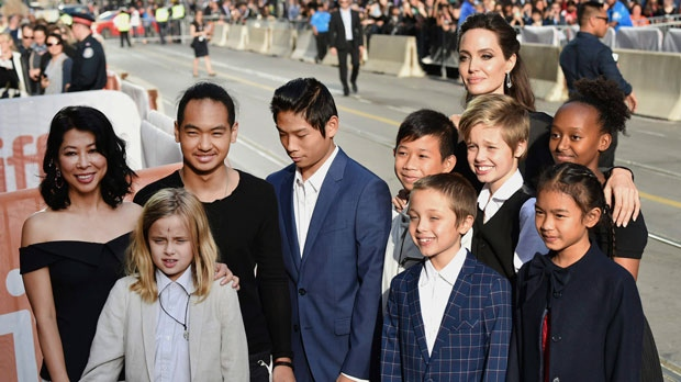 """Vivienne Jolie-Pitt, front row from left, Knox Jolie-Pitt, Sareum Srey Moch, middle row from left, Loung Ung, Maddox Jolie-Pitt, Pax Jolie-Pitt, Kimhak Mun, Shiloh Jolie-Pitt, Zahara Jolie-Pitt and Angelina Jolie attend a premiere for """"First They Killed My Father"""" on day 5 of the Toronto International Film Festival at the Princess of Wales Theatre on Monday, Sept. 11, 2017, in Toronto. (Photo by Evan Agostini/Invision/AP)"""