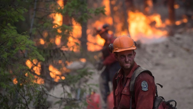 A B.C. Wildfire Service firefighter looks on while conducting a controlled burn to help prevent the Finlay Creek wildfire from spreading near Peachland, B.C., on Thursday, September 7, 2017. THE CANADIAN PRESS/Darryl Dyck