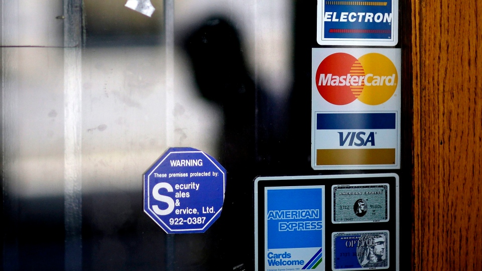 In this July 18, 2012, file photo, a pedestrian walks past credit card logos posted on a downtown storefront in Atlanta. (AP Photo / David Goldman, File)