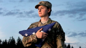 In this Aug. 28, 2015 file photo, Capt. Jennifer Peace holds a flag as she stands for a photo near her home in Spanaway, Wash. (Drew Perine / The News Tribune via AP, File )