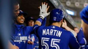 Toronto Blue Jays catcher Russell Martin is greeted in the dugout after scoring the go-ahead run on a Josh Donaldson hit off Minnesota Twins pitcher Ryan Pressly during the seventh inning of a baseball game Friday, Sept. 15, 2017, in Minneapolis.  (AP /Jim Mone)