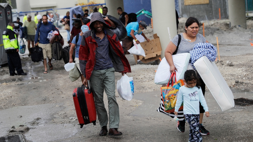 In this Sept. 9, 2017 file photo, evacuees are moved to another building with more bathrooms while sheltering at Florida International University ahead of Hurricane Irma in Miami. (AP Photo/David Goldman)