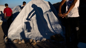 In this Friday, June 9, 2017 photo a Pakistani migrant wrings out a t-shirt near the Souda refugee camp by the beach, where hundreds of refugees and other migrants live in makeshift tents on Chios island, Greece. (AP Photo/Petros Giannakouris)