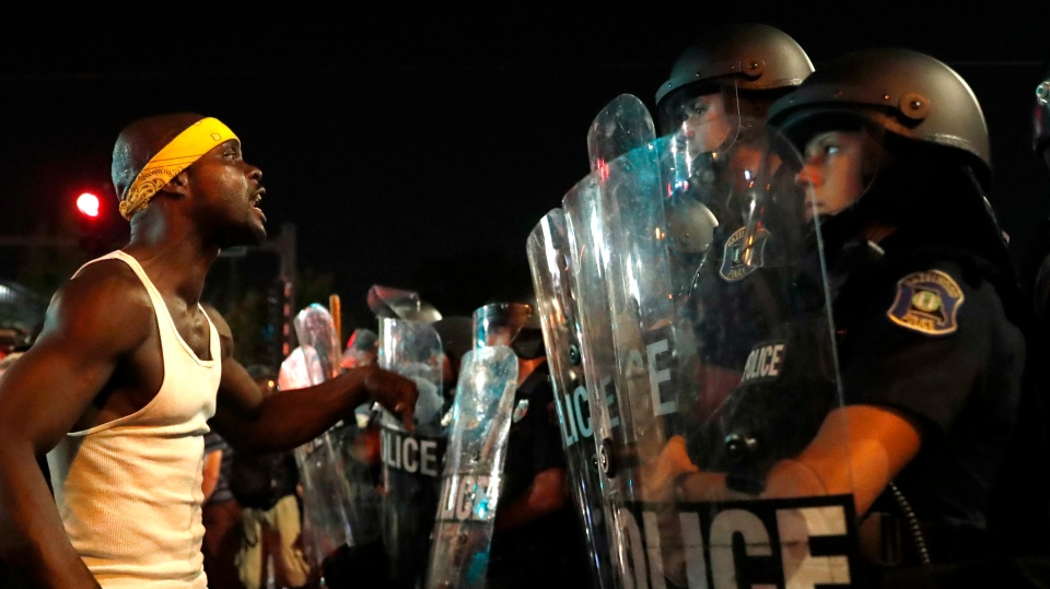 A man yells at police in riot gear just before a crowd turned violent Saturday, Sept. 16, 2017, in University City, Mo. (AP / Jeff Roberson)