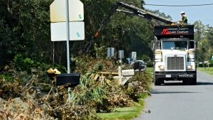 A truck from Graham County Land Company with a claw arm collects debris from piles along Forest Avenue in Neptune Beach, Fla., Sunday, Sept.17, 2017.  (Bob Mack/Florida Times-Union via AP)