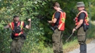 Quebec provincial police officers search the side of a road for evidence into the disappearance of a man and a young boy in Lachute, Que., Friday, September 15 , 2017. (Graham Hughes/The Canadian Press)