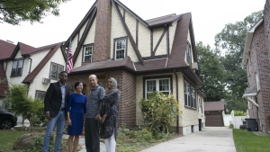 Abdi Iftin, left, of Somalia, Uyen Nguyen, second from left, of Vietnam, Eiman Ali, right, of Somalia born in Yemen, and Ghassan al-Chahada, of Syria pose for a photo outside U.S. President Donald Trump's boyhood home in the Jamaica Estates neighbourhood of the Queens borough of New York on Saturday, Sept. 16, 2017. (AP / Mary Altaffer)