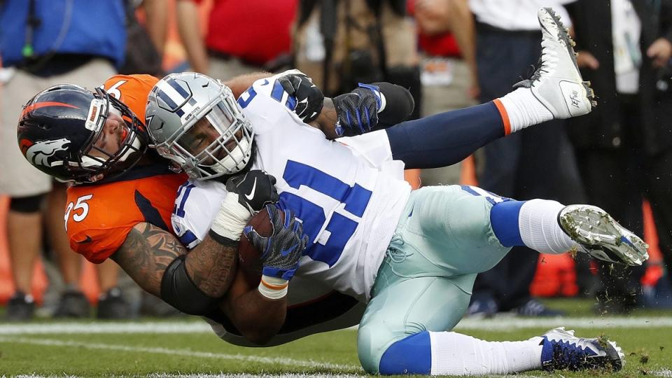 Dallas Cowboys running back Ezekiel Elliott (21) is tackled by Denver Broncos cornerback Chris Harris on Sept. 17, 2017, in Denver. (Jack Dempsey / AP)