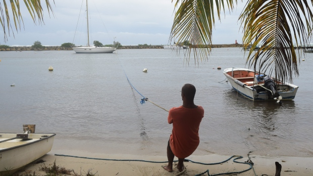 A man pulls in a boat ahead of Hurricane Maria in the Galbas area of Sainte-Anne on the French Caribbean island of Guadeloupe, early Monday, Sept. 18, 2017. (AP Photo/Dominique Chomereau-Lamotte)