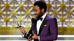 "Donald Glover accepts the award for outstanding directing for a comedy series for the ""Atlanta"" episode ""B.A.N."" at the 69th Primetime Emmy Awards on Sunday, Sept. 17, 2017, at the Microsoft Theater in Los Angeles. (Photo by Chris Pizzello/Invision/AP)"