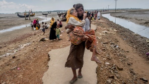 In this Sept. 16, 2017, file photo, Abdul Kareem, a Rohingya Muslim man, carries his mother, Alima Khatoon, to a refugee camp after crossing over from Myanmar into Bangladesh, at Teknaf, Bangladesh. (AP Photo/Dar Yasin, File)