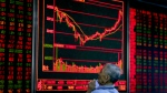 A Chinese man holds his smartphone displaying stock index as he monitors stock prices at a brokerage house in Beijing on Monday, Sept. 18, 2017. (AP / Andy Wong)