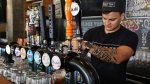 In this Sunday, Sept. 10, 2017 photograph, bartender Michael Zakharchenko, originally from Ukraine, pours a beer at the Black Tap restaurant in Dubai, United Arab Emirates. (AP Photo/Jon Gambrell)