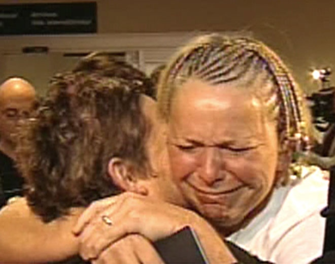 Brenda Grenier, one of 159 passengers held hostage aboard a plane in Jamaica, embraces members of her family upon her return to Canada on Monday, March 20, 2009.