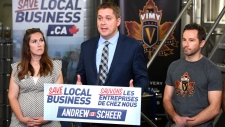 Conservative Party Leader Andrew Scheer stands with dairy farmer Melinda Foster Marshall, left, and Vimy Brewing Company co-founder Kevin Sirko, right, at a press conference launching the Save Local Business campaign in response to the government's tax changes for small businesses, at the Vimy Brewing Company in Ottawa on Tuesday, Sept. 19, 2017. (Justin Tang/THE CANADIAN PRESS)