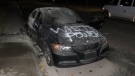 Calgary police are looking for suspects after a BMW, parked outside a northeast home, was tagged with racist graffiti and set on fire. (CPS)